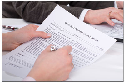womens hand holding a power of attorney form and pen